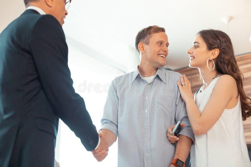 Mari serrant la main de l'agent immobilier après l'achat de la maison avec l'épouse photographie stock libre de droits