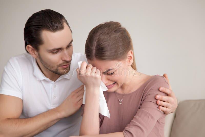 Mari soulageant l'épouse pleurante triste, jeune sanglotant de consolation d'homme photographie stock