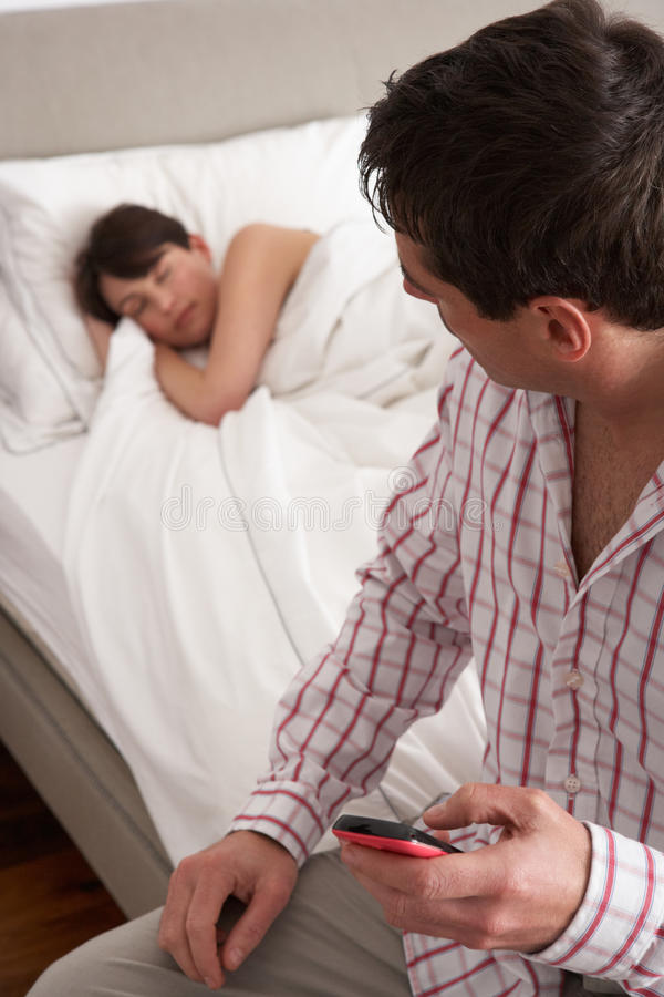 Mari soupçonneux contrôlant le téléphone portable de l'épouse photographie stock