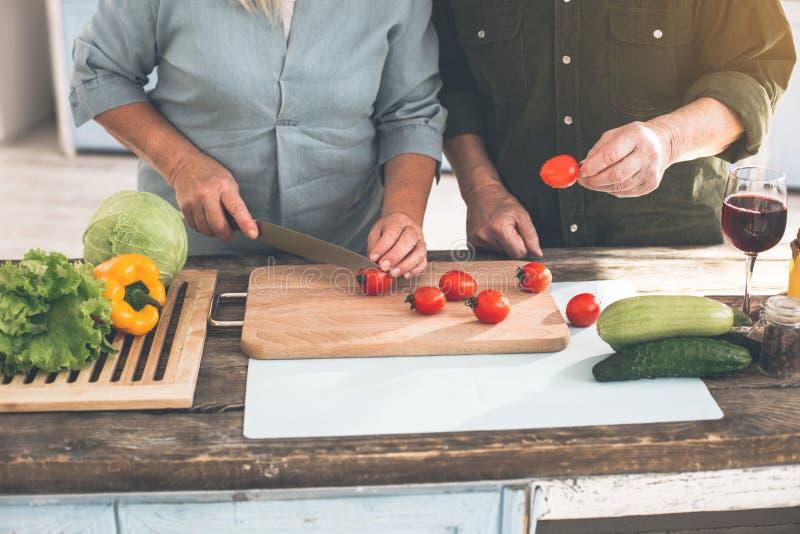 Mari supérieur et épouse préparant la nourriture dans la cuisine images libres de droits