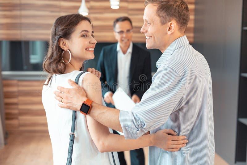 Mari utilisant la montre intelligente étreignant l'épouse tout en achetant la maison photographie stock libre de droits
