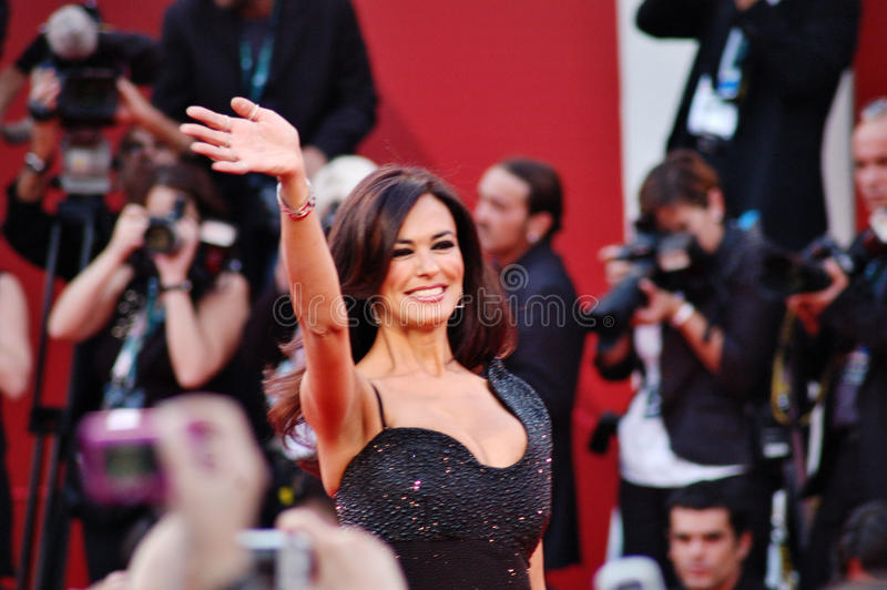 Maria Grazia Cucinotta says hallo. Maria Grazia Cucinotta smiling and saying hallo on the red carpet for the official awards. She hosted the 66th Venice Film stock image