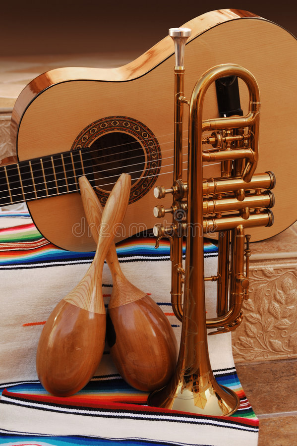 Mariachi. Accoustic guitar, maracas and trumpet on mexican fabric