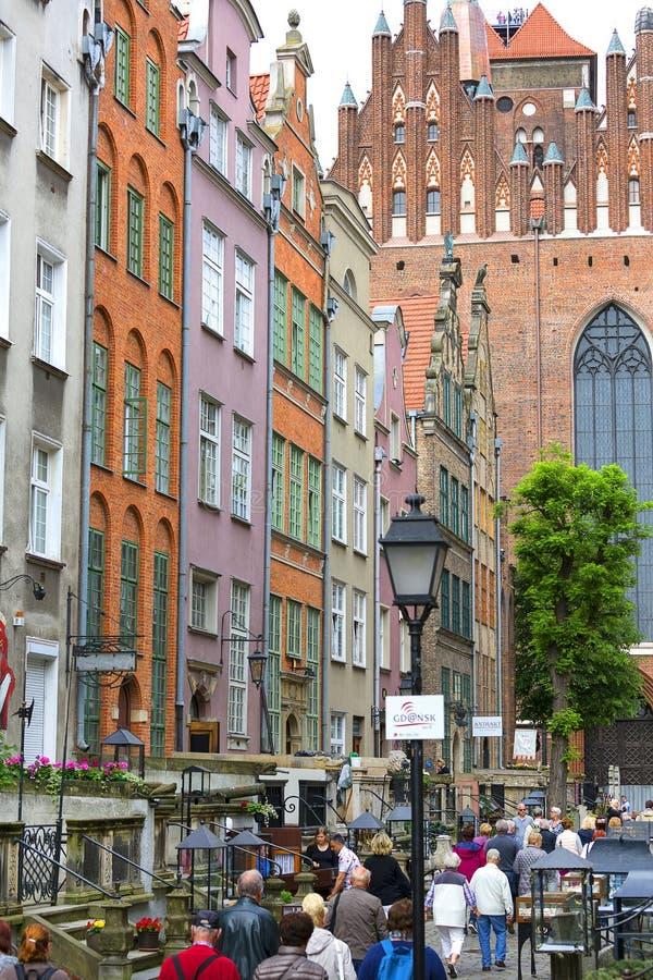 Mariackastraat met kleurrijke voorgevels van huurkazernes en de 16de eeuw gotische St Mary ` s Kerk, Gdansk, Polen stock fotografie