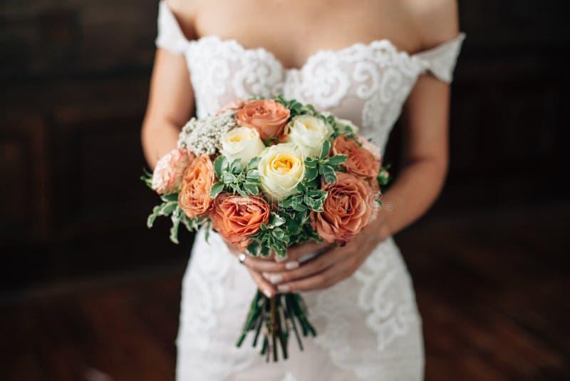 mariage Bouquet dans la main de jeune mariée Jeune mariée dans la robe sexy de wtite avec les lèvres rouges sur le fond foncé photo libre de droits