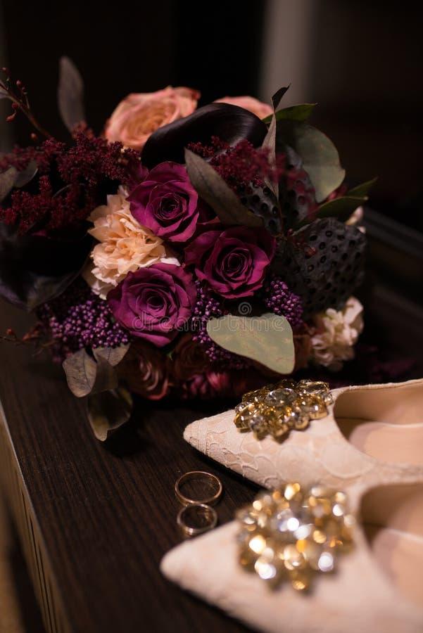 mariage Bouquet nuptiale dans des couleurs de marsala et près des chaussures d'un beige avec les pierres brillantes sur elles photos libres de droits