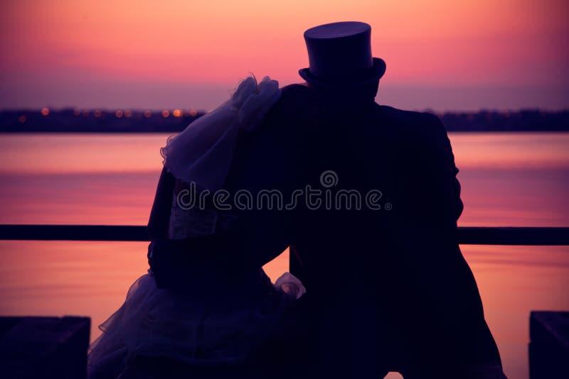 Mariage de couples regardant le coucher du soleil photo stock