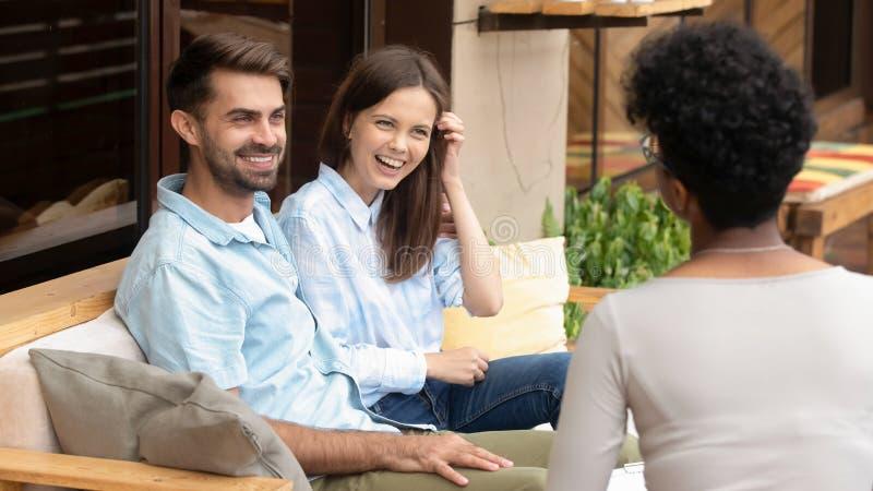 Mariage de planification de jeunes couples caucasiens heureux écoutant le planificateur africain image libre de droits