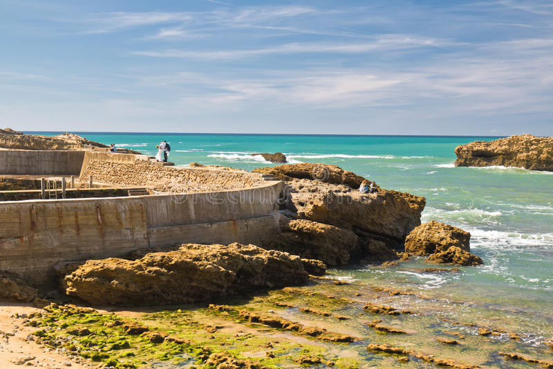 Mariage des jeunes mariés se tenant sur la roche sur la côte atlantique colorée scénique en ciel bleu à Biarritz, pays Basque, photo libre de droits