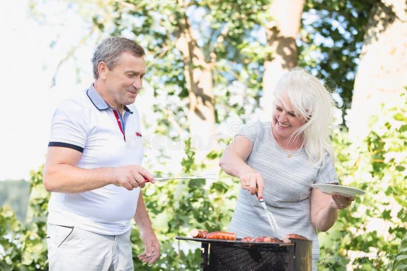 Mariage plus âgé grillant la viande ensemble photo libre de droits