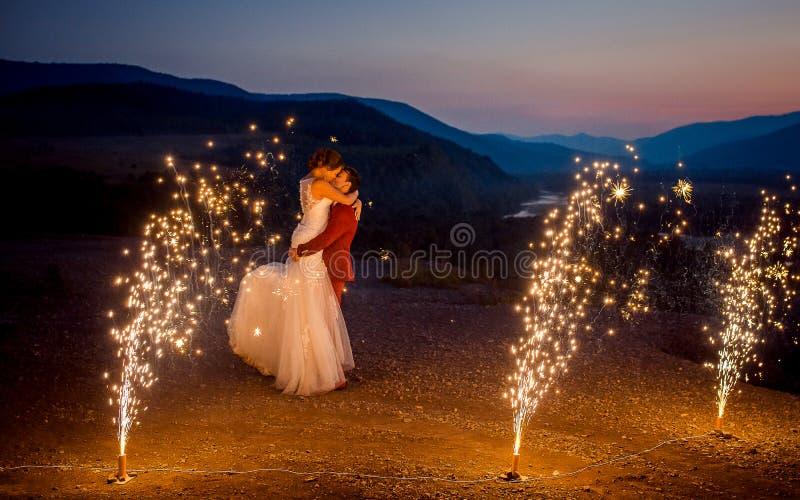 Mariage romantique tiré des nouveaux mariés de baiser Le marié se soulève vers le haut de la jeune mariée sur les montagnes décor photo stock