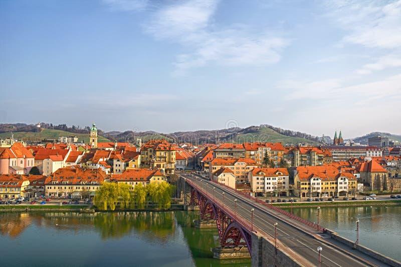 Maribor - Main bridge and Lent. Maribor, Slovenia, Europe. Main bridge (Glavni most, Stari most) over the Drava river. Popular riverbank Lent in the background royalty free stock photography
