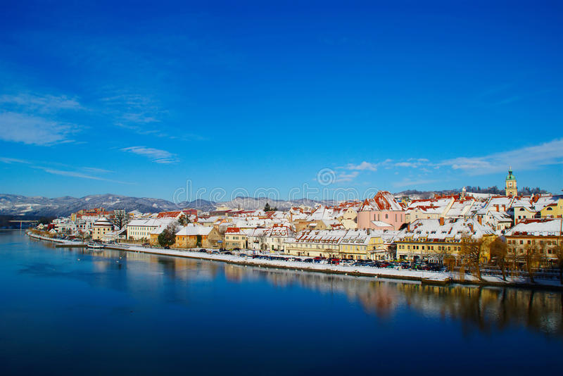 Maribor In Winter. Historic quarter Lent in Maribor, Slovenia on Drava river on sunny winter day under blue sky with buildings covered with fresh snow stock photos