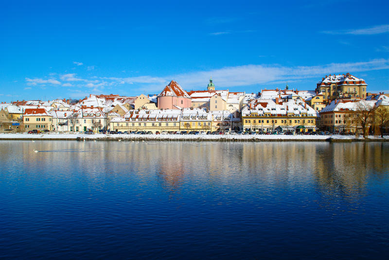 Maribor In Winter. Historic quarter Lent in Maribor, Slovenia on Drava river on sunny winter day under blue sky with buildings covered with fresh snow stock photo
