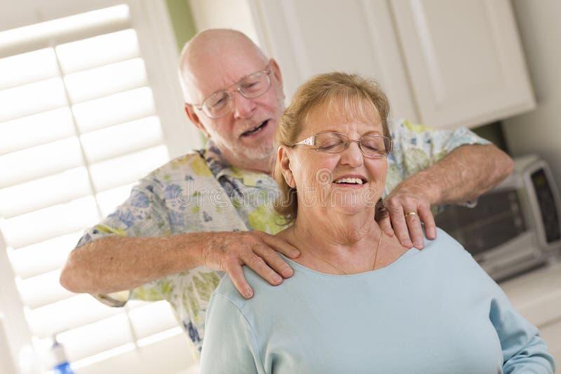 Marido adulto superior que dá a esposa uma RUB do ombro imagens de stock royalty free