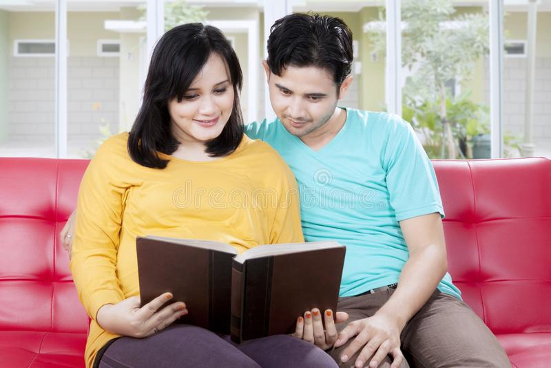 Marido cariñoso que lee un libro con la esposa embarazada fotografía de archivo