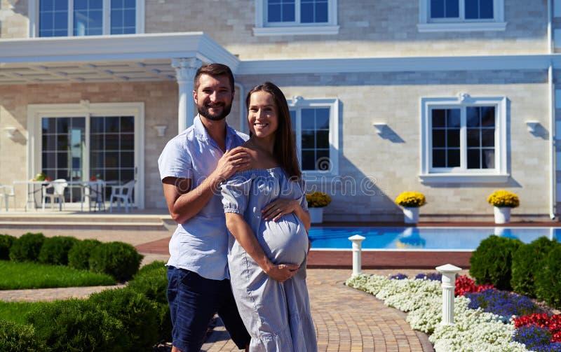 Marido cariñoso y esposa embarazada que presentan delante de nuevo h moderno imágenes de archivo libres de regalías