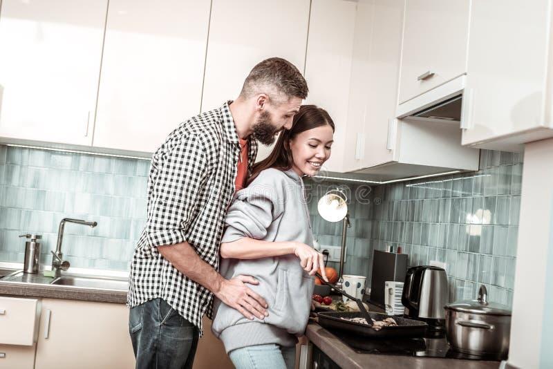 Marido de amor que abraça sua amiga que cozinha o café da manhã para ele foto de stock royalty free