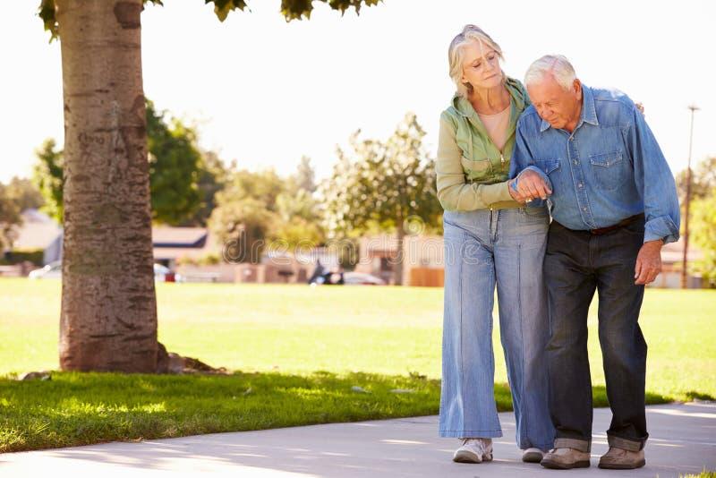 Marido de ayuda de la mujer mayor como caminan en parque juntos imágenes de archivo libres de regalías