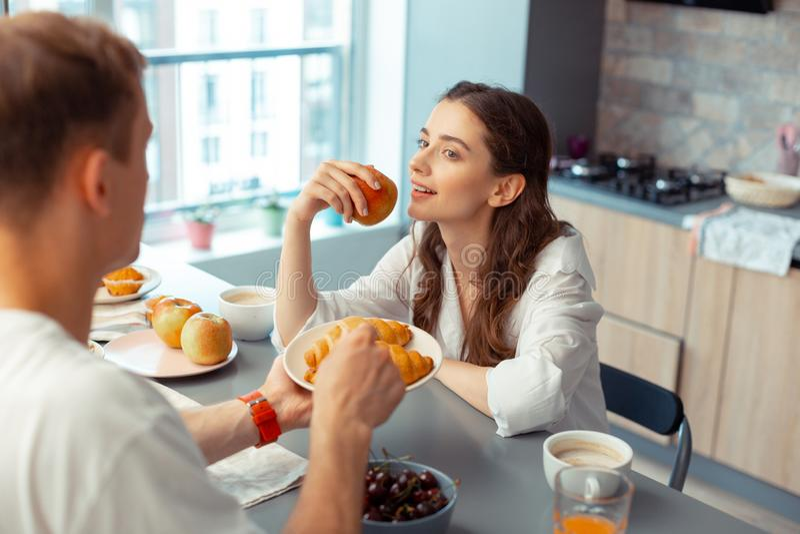 Marido de cabelo escuro que dá croissant para a esposa que come a maçã imagens de stock royalty free