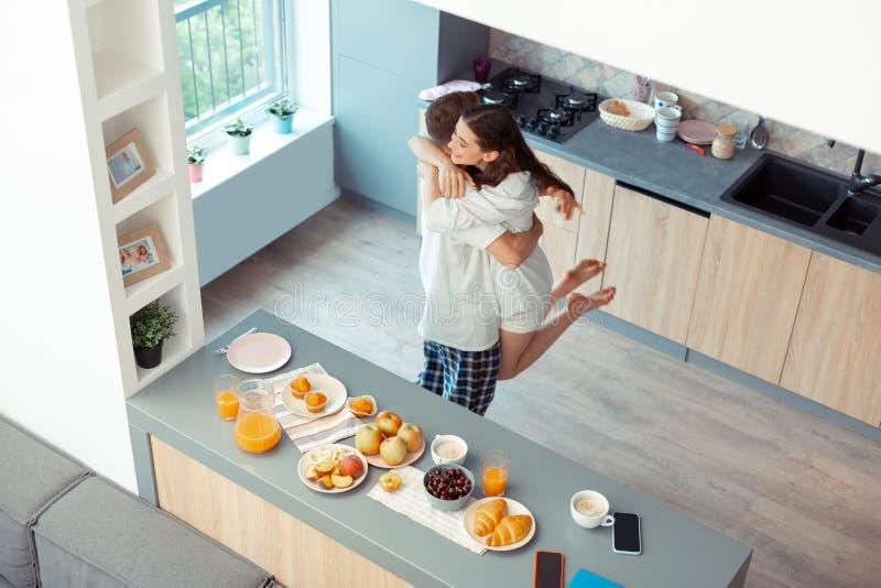 Marido de cabelo escuro que levanta sua esposa feliz na cozinha fotografia de stock royalty free
