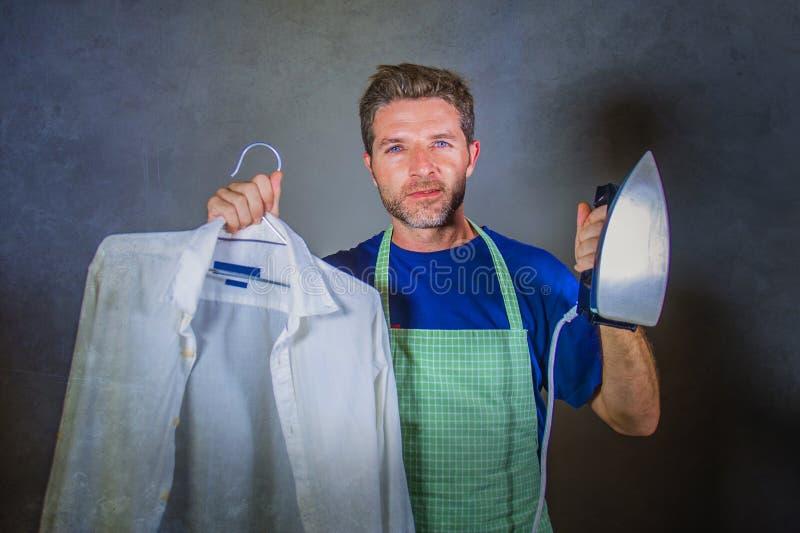 Marido de casa feliz y orgulloso atractivo joven o solo hombre que sostiene el hierro que muestra la camisa después de planchar e foto de archivo