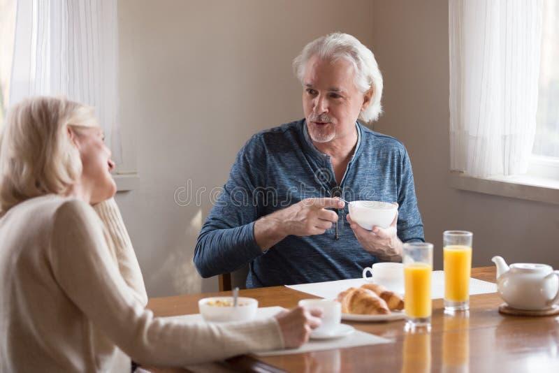 Marido e esposa envelhecidos felizes para apreciar em casa o café da manhã imagem de stock royalty free