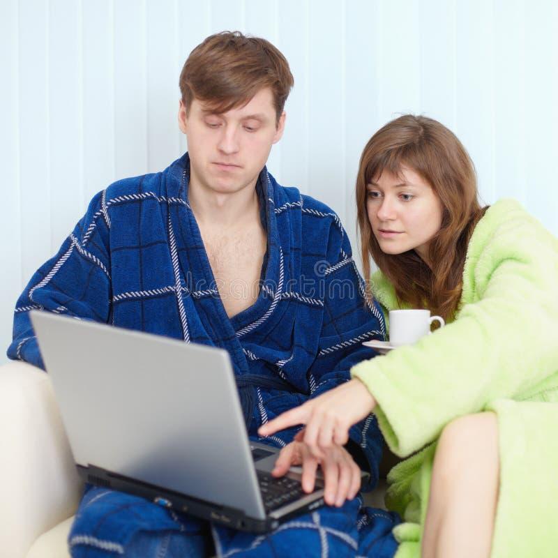 Marido e esposa na casa no sofá com portátil foto de stock