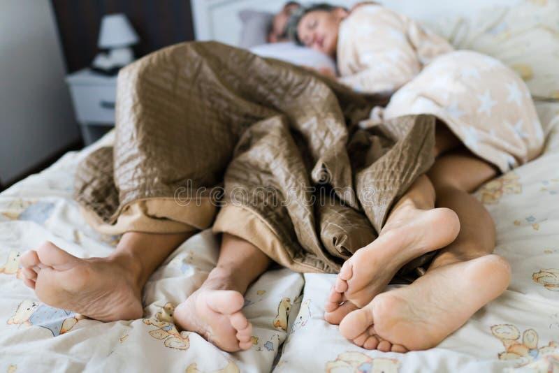 Marido e esposa que dormem na cama junto coberta parcialmente fotografia de stock royalty free