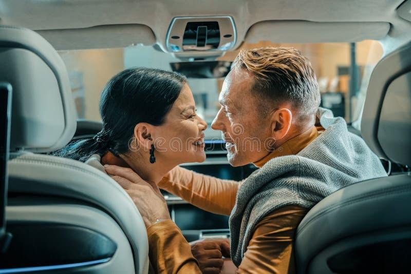 Marido e esposa que sorriem antes de beijar no carro imagens de stock royalty free