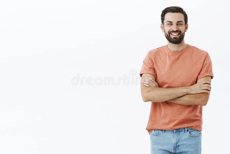 Marido farpado despreocupado bonito feliz no t-shirt ocasional que mantém as mãos cruzadas sobre a caixa, o riso e o sorriso fotografia de stock royalty free