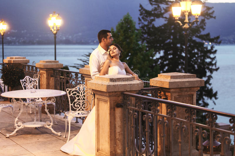 Marido feliz e esposa dos pares que abraçam no balcão no nivelamento próximo foto de stock royalty free