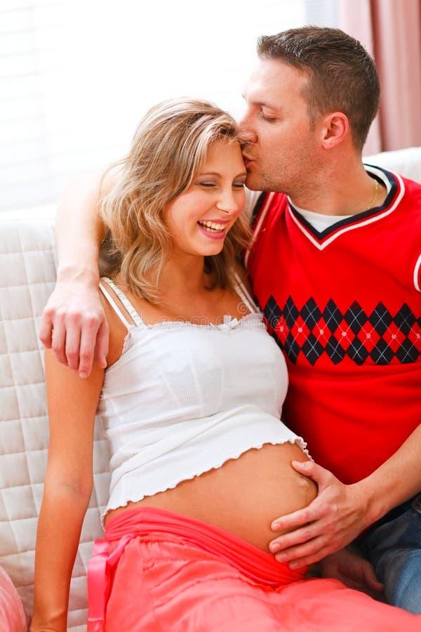 Marido feliz que beija a esposa grávida fotos de stock