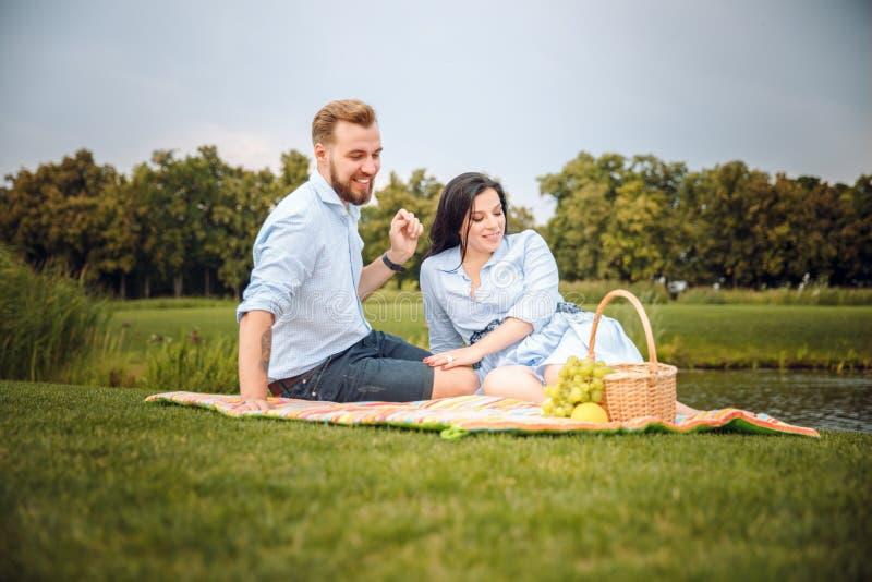 Marido joven alegre feliz de la familia y su esposa embarazada que se divierten junto al aire libre, en la comida campestre en pa imagen de archivo