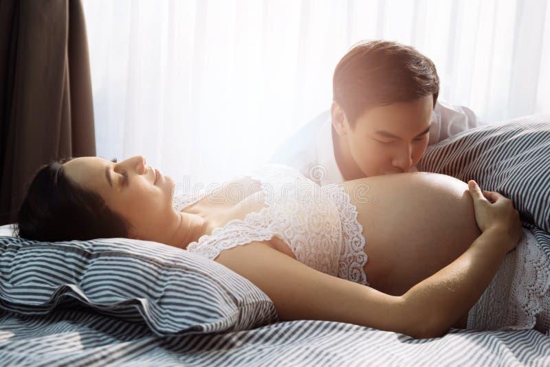 Marido joven que se besa en la panza de la esposa embarazada imágenes de archivo libres de regalías