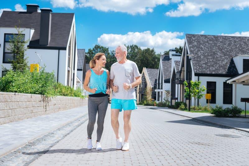 Marido maduro farpado que junta-se a sua esposa magro bonita que corre na manhã foto de stock