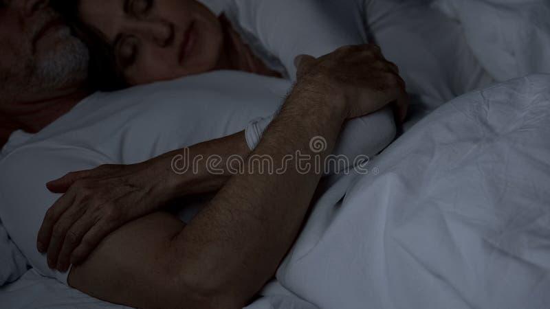 Marido mayor y esposa que abrazan en la señora de la cama que miente en matrimonio fuerte del pecho masculino imágenes de archivo libres de regalías