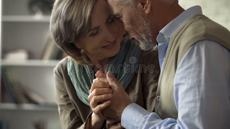 Marido mayor y esposa que miran uno a con el amor, llevando a cabo las manos, matrimonio fotografía de archivo libre de regalías