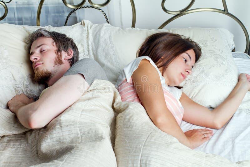 Marido novo e esposa que dormem na cama no quarto fotografia de stock royalty free