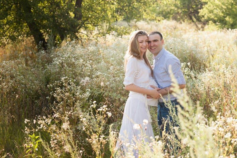 Marido que abraza a la esposa embarazada del vientre, amor, anticipación, actitud, forma de vida foto de archivo