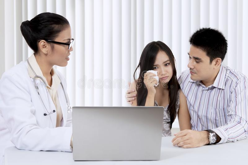 Marido que conforta a la esposa después de oír malas noticias de un doctor imagen de archivo