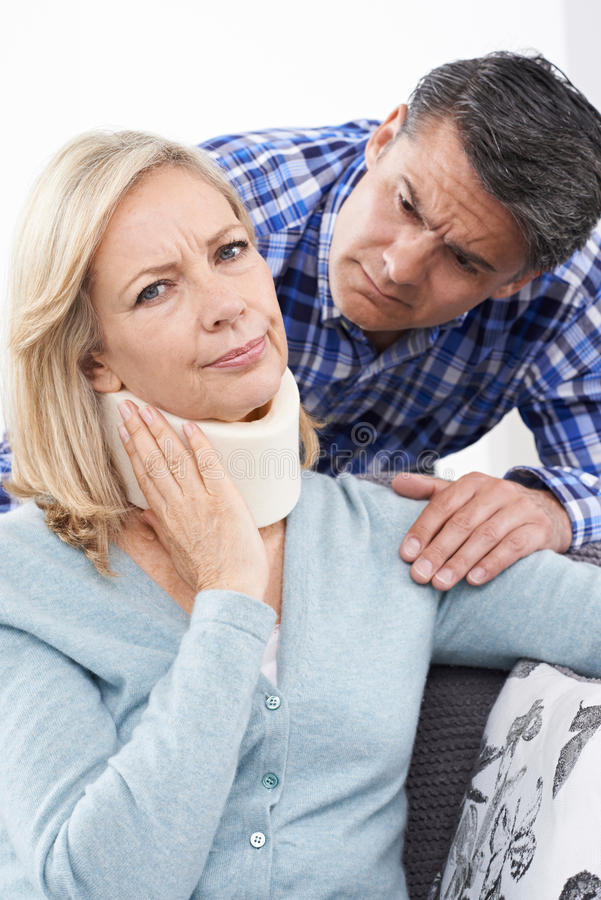 Marido que conforta a la esposa que sufre con lesión del cuello imagen de archivo