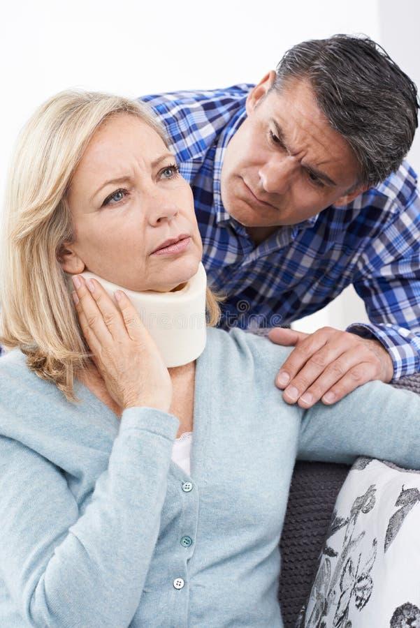 Marido que conforta a la esposa que sufre con lesión del cuello fotos de archivo libres de regalías