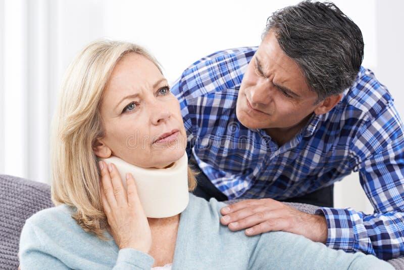 Marido que conforta a la esposa que sufre con lesión del cuello imágenes de archivo libres de regalías