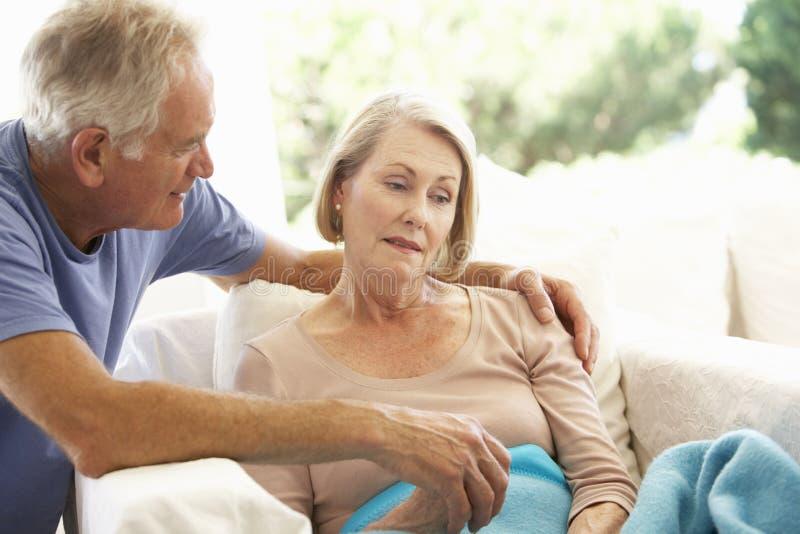 Marido que conforta a la mujer mayor que siente la reclinación mal debajo de la manta fotos de archivo