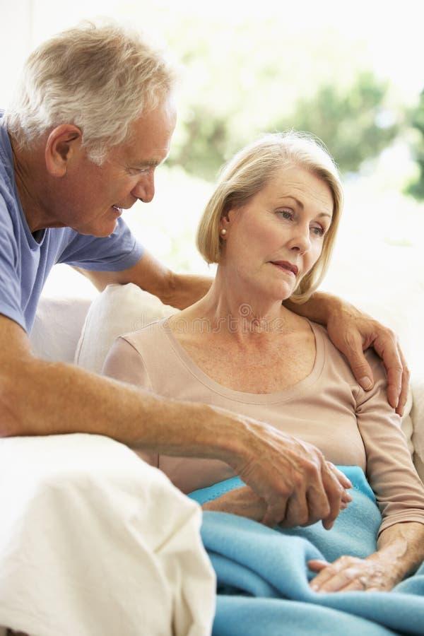 Marido que conforta a la mujer mayor que siente la reclinación mal debajo de la manta imagen de archivo