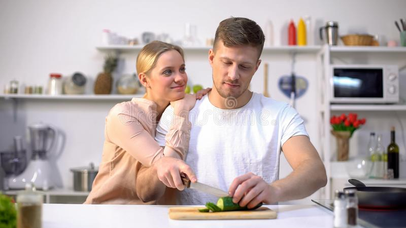 Marido que corta o vegetal, esposa de amor que abraça o, momento romântico na cozinha imagem de stock royalty free