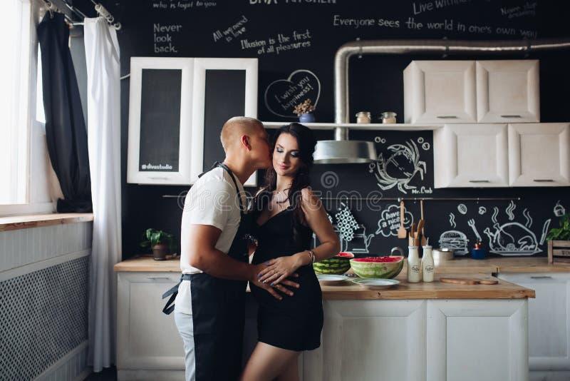 Marido que cozinha o jantar para a esposa grávida adorável em casa foto de stock royalty free