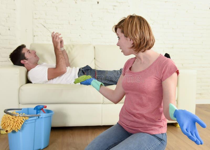 Marido que descansa sobre el sofá mientras que limpieza de la esposa que hace el quehacer doméstico en concepto del chauvinismo foto de archivo libre de regalías
