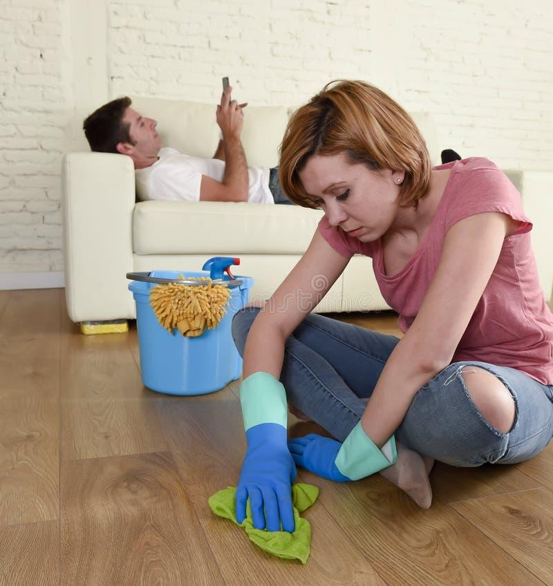 Marido que descansa sobre el sofá mientras que limpieza de la esposa que hace el quehacer doméstico en concepto del chauvinismo imagen de archivo